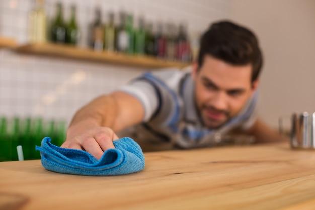 Absolute sauberkeit. selektiver fokus eines blauen staubtuchs, der zum reinigen der oberfläche der theke verwendet wird