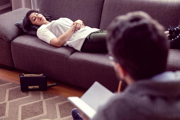 Absoluter komfort. schöne schöne frau, die auf dem sofa liegt, während sie eine psychologische sitzung hat