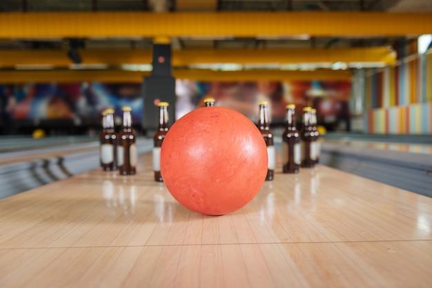 Absoluter streik. selektiver fokus einer bowlingkugel, die flaschen mit bier schlägt