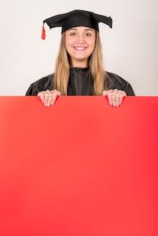 Absolvent, der rotes plakatmodell lächelt und hält