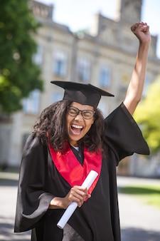 Absolvent. eine studentin, die sich über den college-abschluss großartig fühlt