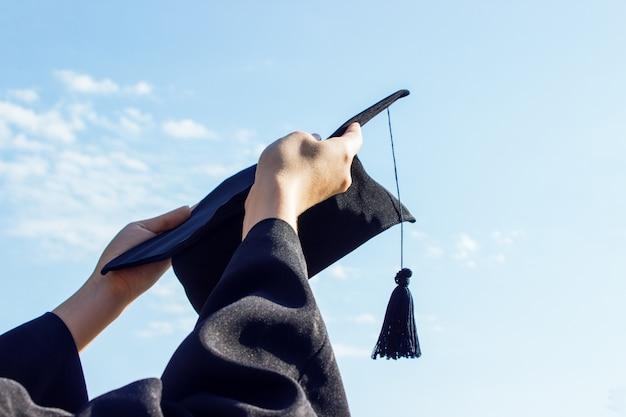 Absolvent feiert mit mütze in der hand