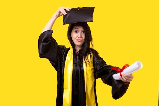 Absolvent mit einem diplom in der hand, verzieht das gesicht und freut sich über den erfolgreichen abschlusstag, bild auf einer gelben wand