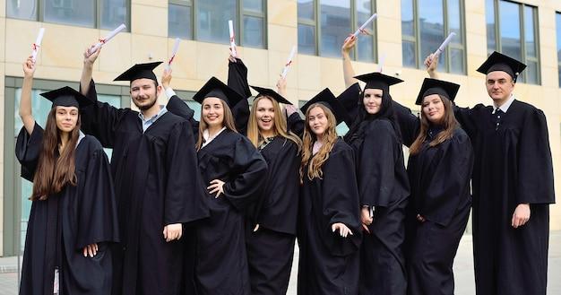 Absolventen in schwarzen studentenroben und eckigen hüten freuen sich über diplome und beenden den ausbildungsprozess. höhere bildung