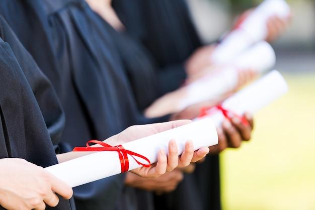 Absolventen mit diplom. nahaufnahme von vier hochschulabsolventen, die in einer reihe stehen und ihre diplome halten