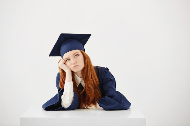 Absolventin der rothaarigen im mantel, der das sitzen denkt.
