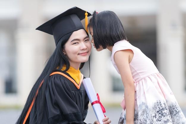 Absolventin mit kleinem mädchen an ihrem abschlusstag