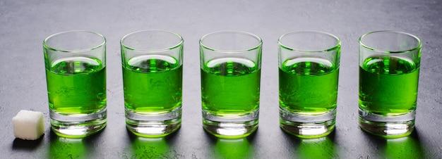 Absorbieren sie die grüne flüssigkeit in gläsern. alkoholisches halluzinogenes getränk. dunkler hintergrund. stücke weißzucker