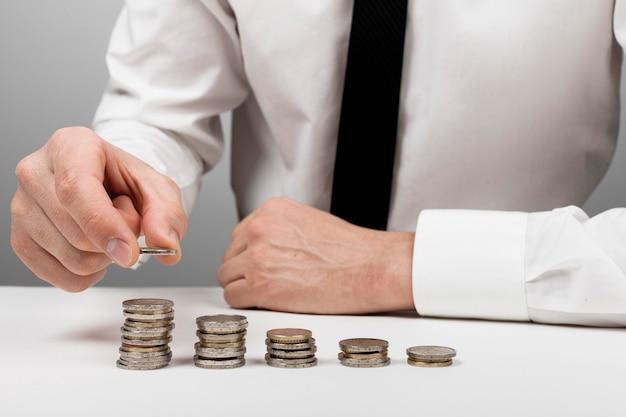 Absteigende stapel von münzen und geschäftsmann
