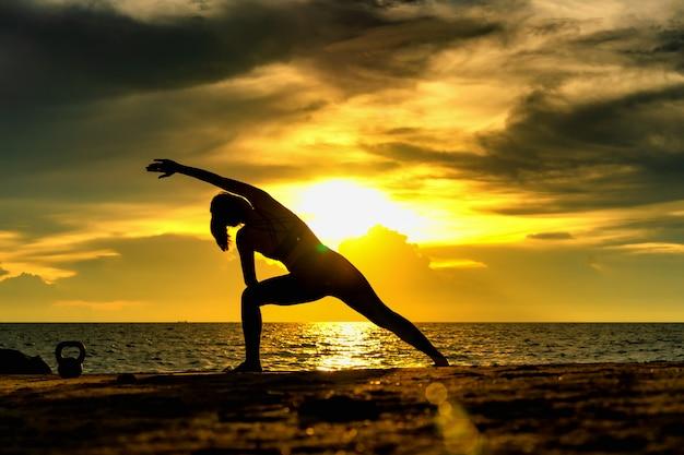 Abstrac. schattenbildyoga porträt übenden yoga der jungen frau in dem meer. entspannen sie sich in dem meer