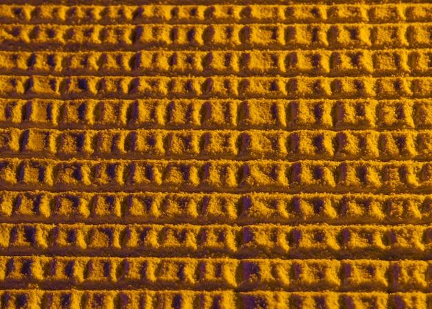 Abstrakte bienenwabe mit gelbem sand