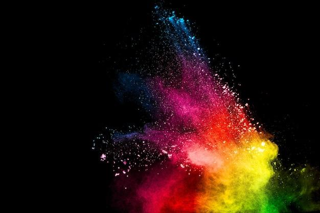 Abstrakte bunte pulverexplosion auf schwarzem hintergrund. frostbewegung des staubspritzens. gemaltes holi.