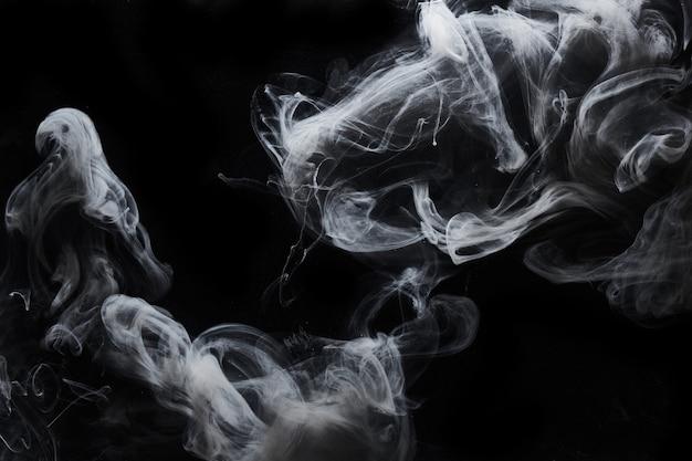 Abstrakte dunkle farbe im wasserhintergrund. weiße rauchwolkenbewegung auf schwarzen, wirbelnden acryltintenspritzern