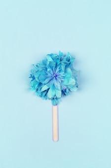Abstrakte eiscreme, blaue blume auf hölzernem eiscremestock auf hellblauem