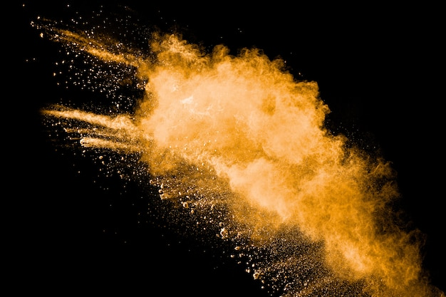 Abstrakte explosion des orange staubes auf schwarzem hintergrund. frieren sie bewegung des orange pulverspritzens ein.