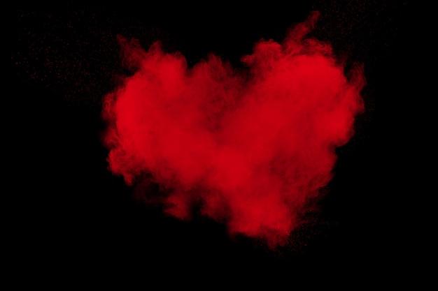 Abstrakte explosion des roten pulvers auf schwarzem hintergrund. rotes herz.