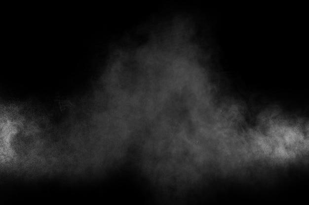 Abstrakte explosion des weißen pulvers auf einem schwarzen hintergrund
