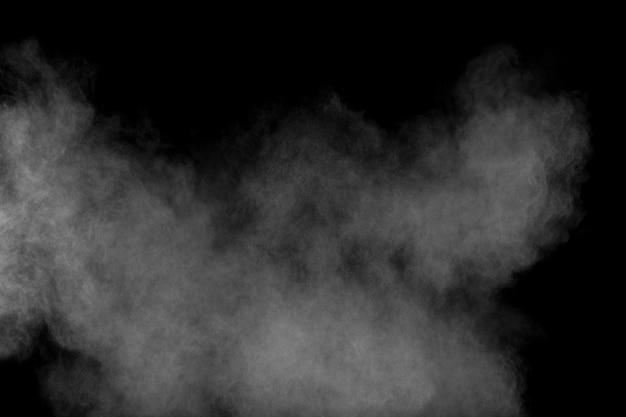 Abstrakte explosion des weißen pulvers gegen schwarzen hintergrund. abstrakter weißer staub atmen aus.