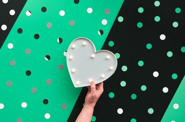 Abstrakte fahne oder kartenschablone mit konfetti, tupfen. hand hält herzförmigen leuchtkasten. überlagertes papier mit grüner, weißer und schwarzer diagonale.