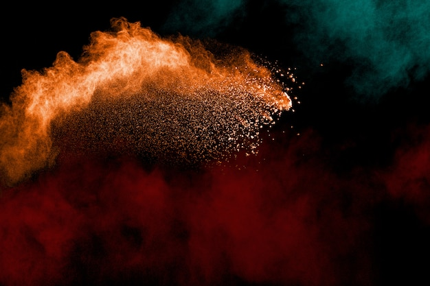 Abstrakte farbpulverexplosion auf schwarzem hintergrund. bewegung des staubspritzens einfrieren.