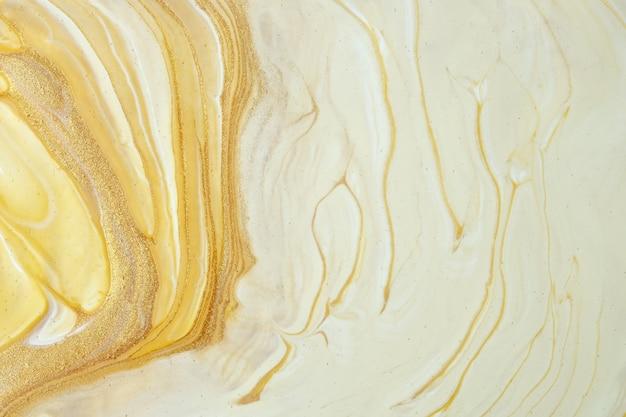 Abstrakte fließende kunsthintergrund hellgelbe und goldene farben. flüssiger marmor