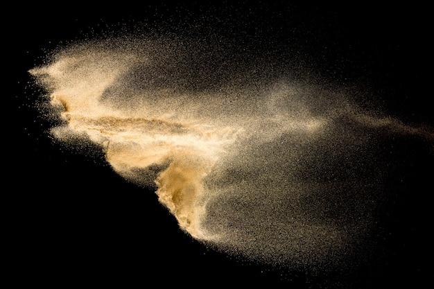 Abstrakte flusssandwolke. goldenes farbiges sandspritzen gegen schwarzen hintergrund.