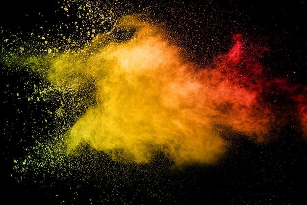 Abstrakte gelb-orangee pulverexplosion auf schwarzem
