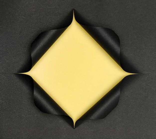 Abstrakte gelbe form auf zerrissenem schwarzem papier