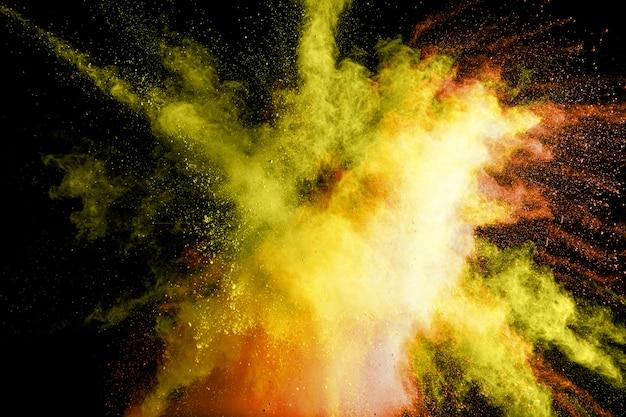 Abstrakte gelbe pulverexplosion. bewegung des gelben staubspritzens einfrieren.