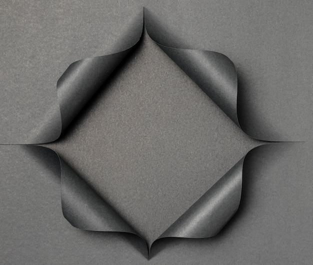 Abstrakte graue form auf zerrissenem schwarzem papier