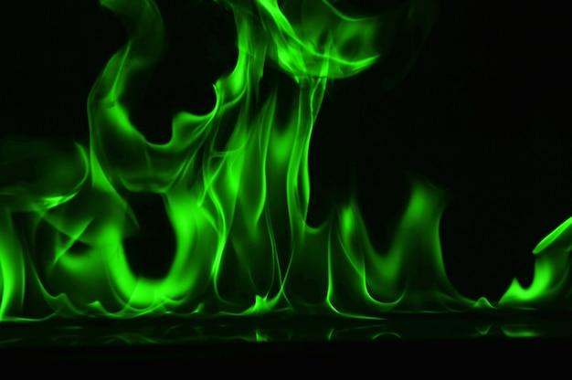 Abstrakte grüne feuerflammen auf schwarzem hintergrund