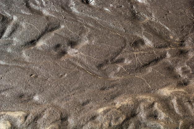 Abstrakte hintergrundbeschaffenheit des nassen sandes und des lehms