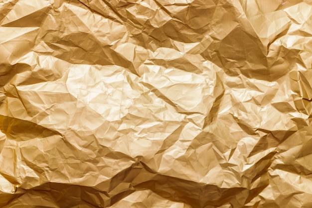 Abstrakte hintergrundtextur golden glänzend gefaltetes folienblech.