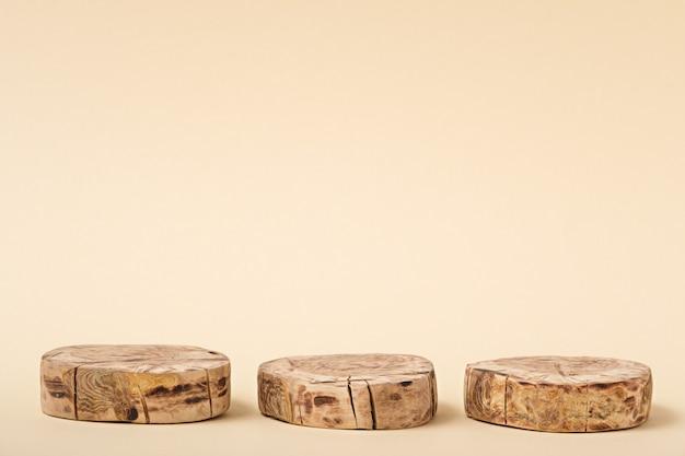 Abstrakte holzplattform mit drei kreisen auf beigem hintergrund