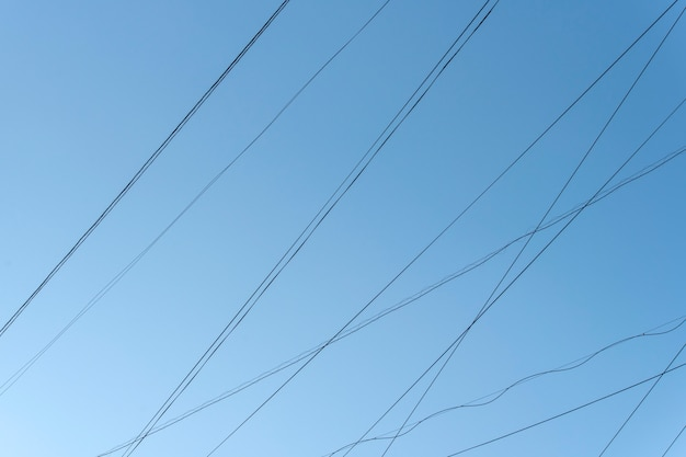 Abstrakte linien von elektrischen kabel-drähten mit blauem himmel in der stadt