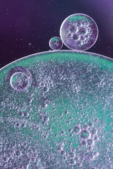 Abstrakte luftblasen und öl fällt in flüssigkeit auf unscharfem hintergrund