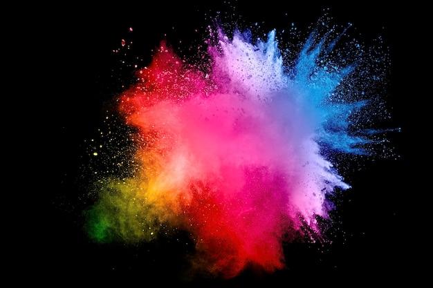 Abstrakte mehrfarbenpulver-explosion auf schwarzem hintergrund. frostbewegung von farbstaubpartikeln spritzen. gemalte holi.