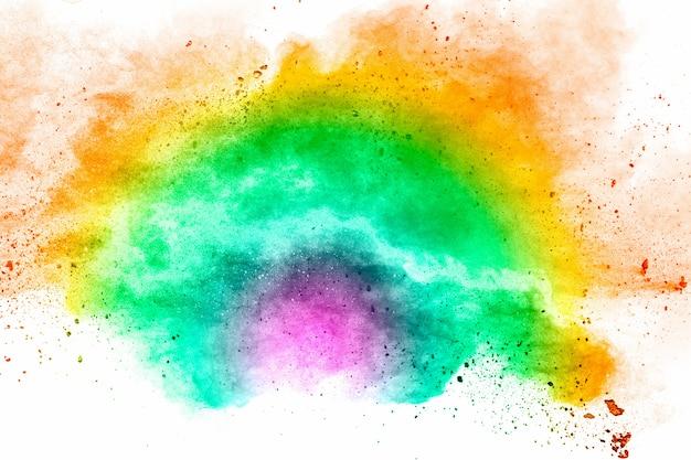 Abstrakte mehrfarbenpulver-explosion auf weißem hintergrund. gefrierbewegung von staubpartikeln spritzen.