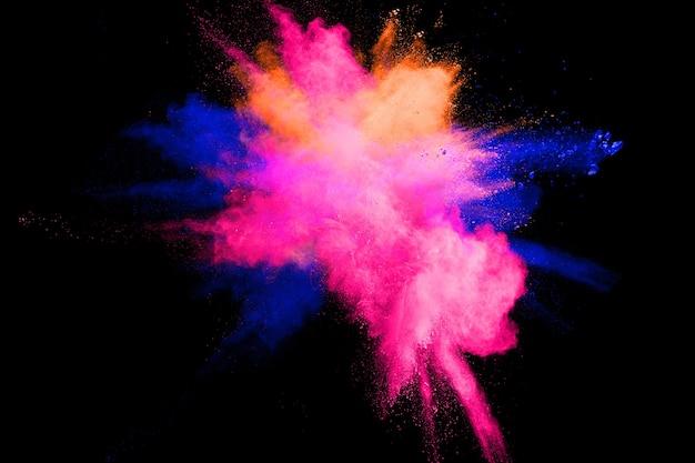 Abstrakte mehrfarbige pulverexplosion auf schwarzem hintergrund.