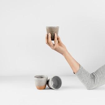 Abstrakte minimale küchenhand, die tasse hält