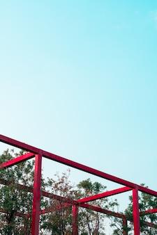 Abstrakte minimale rote metallbefestigungsarchitektur im baumpark, geomatric form construc der kunst