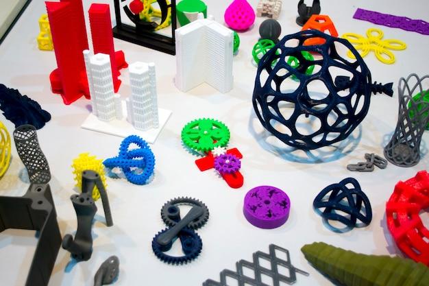 Abstrakte modelle, die von 3d-druckernahaufnahme gedruckt werden. helle bunte objekte, die auf einem 3d-drucker auf einem weißen tisch gedruckt wurden. fortschrittliche moderne additivtechnologie. konzept der industriellen revolution 4.0