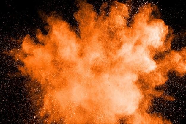 Abstrakte orange pulverexplosion. bewegung des orangefarbenen staubspritzens einfrieren.