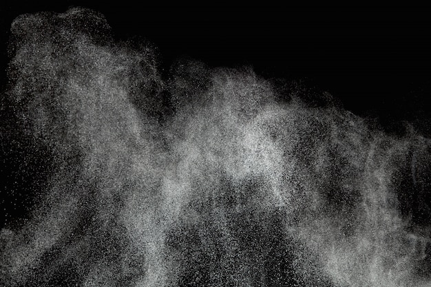 Abstrakte pulverexplosionen lokalisiert auf schwarzem hintergrund.