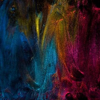 Abstrakte pulverfarben spritzten über schwarzem hintergrund