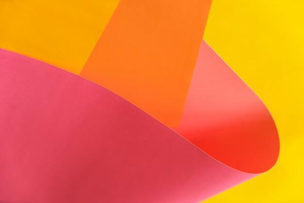 Abstrakte rosa, orange und gelbe papiere, die zusammen in abstrakte form verbiegen. abstrakter farbpapierhintergrund.