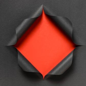 Abstrakte rote form auf zerrissenem schwarzem papier