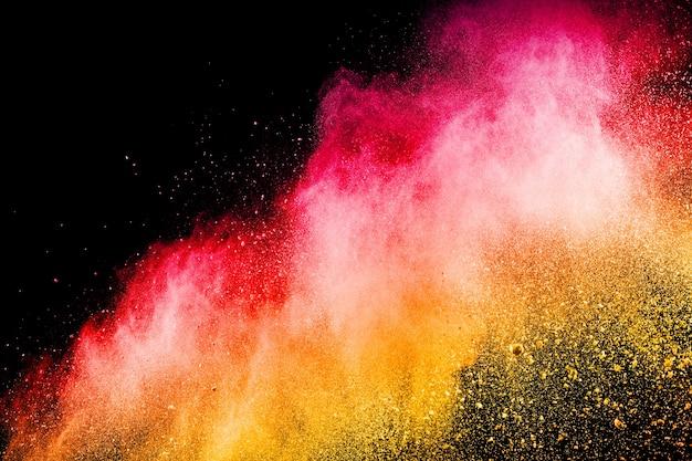 Abstrakte rote gelbe staubexplosion auf schwarzem hintergrund.