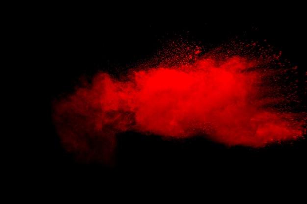 Abstrakte rote staubexplosion auf schwarzem hintergrund. bewegung des roten pulverspritzers einfrieren.