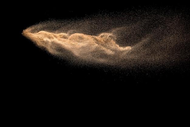 Abstrakte sandwolke. goldenes farbiges sandspritzen gegen dunklen hintergrund.